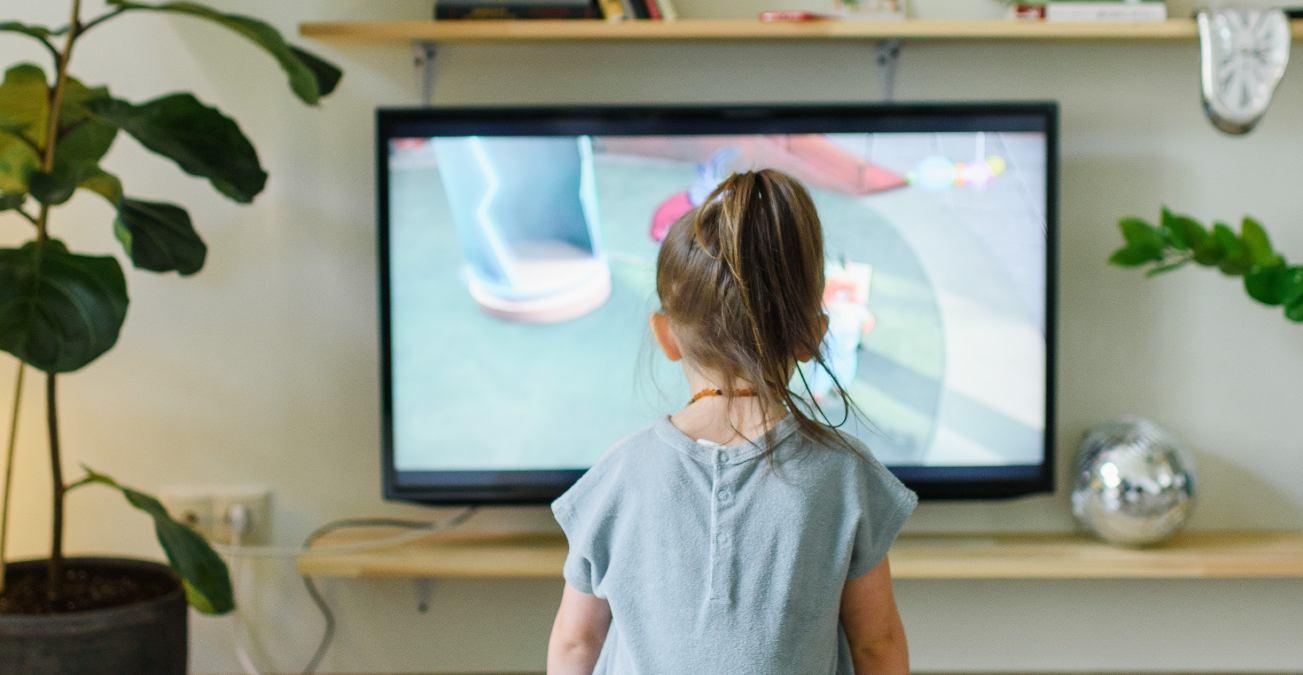 Niña sentada mira fijamente al televisión el 31 de marzo