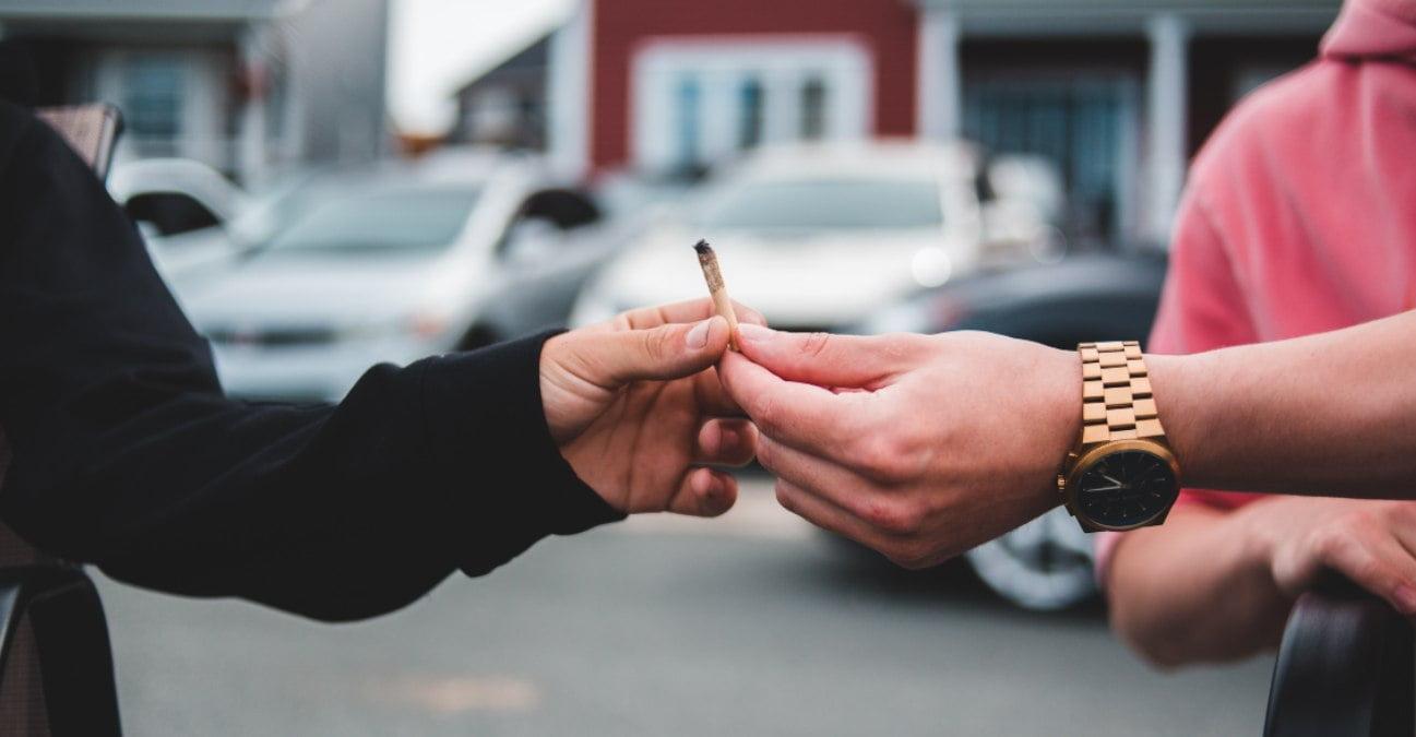 Dos personas se pasan un porro de marihuana