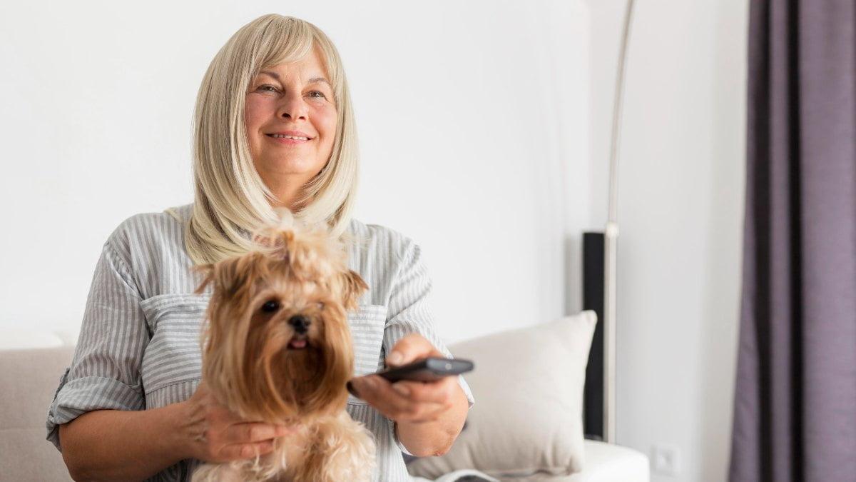 Mujer anciana ve la televisión con su perro el 1 de mayo