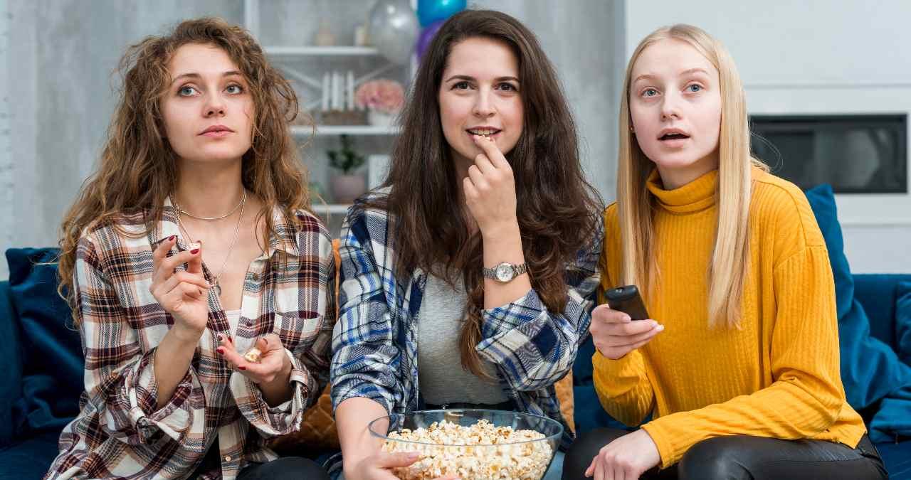 Tres mujeres ven la televisión y comen palomitas el 16 de mayo