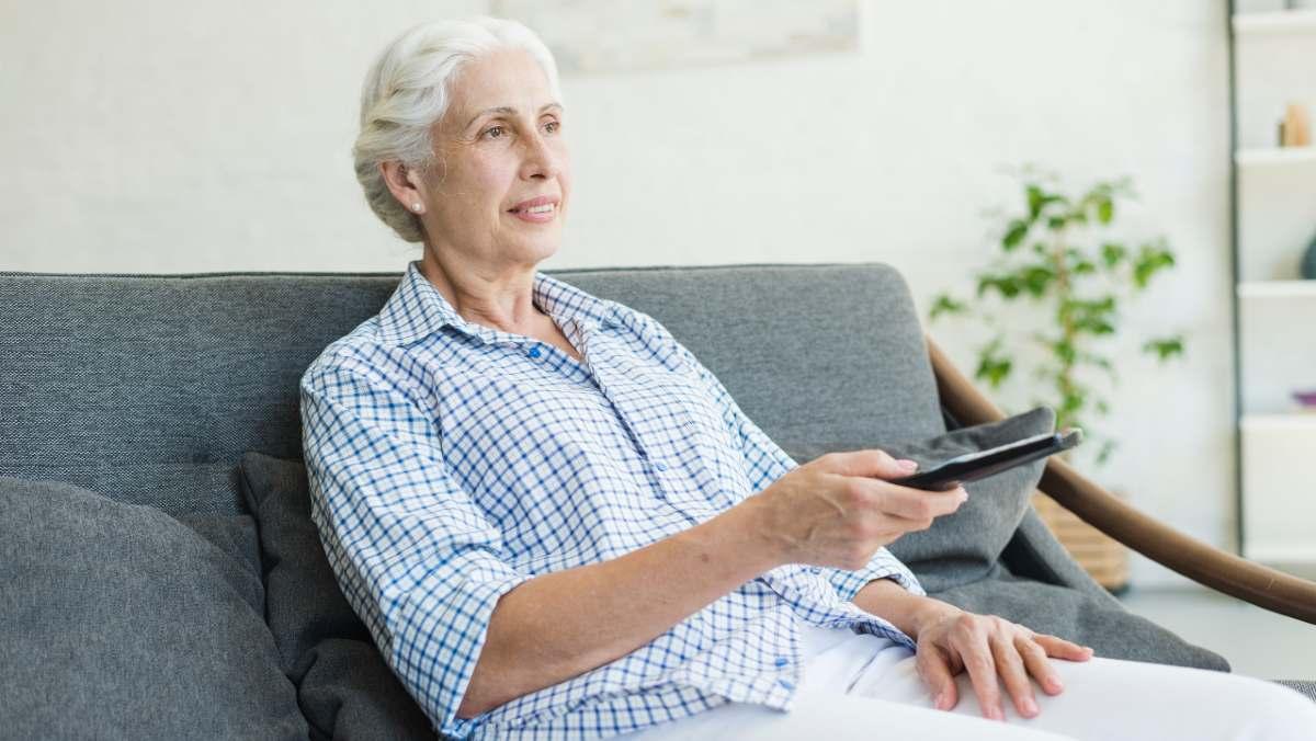 Señora anciana ve la televisión el 5 de mayo