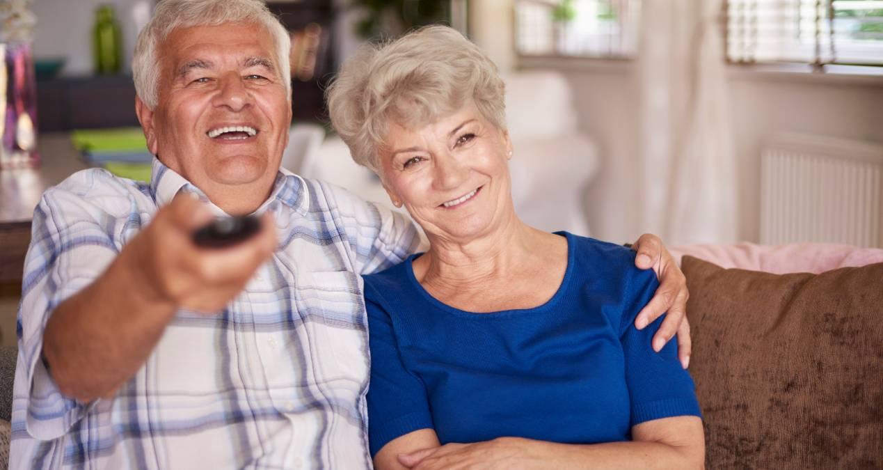 Pareja de personas mayores ve la televisión el 19 de junio